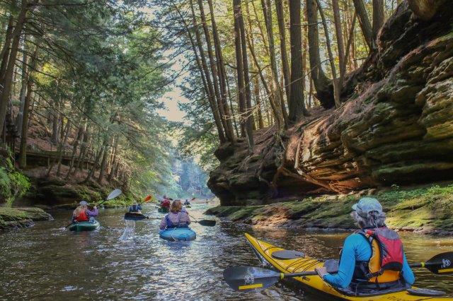 Photo of kayakers as they exist a high-walled gorge in the Dells. Photo by Patty Henry