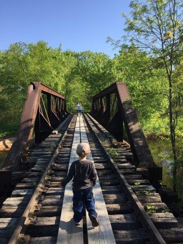 Photo of child looking across a bridge. Taken during Tiffany Bottoms train ride Field Trip. Photo by Charity Hohlstein.